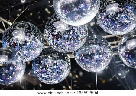 many disco ball on a gray ceiling
