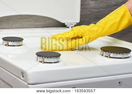 Hand In Yellowglove Cleaning White Stove With Yellow Sponge