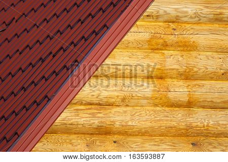 Wooden house wall from logs and part of red roof from metal tile closeup