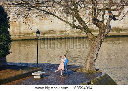 Romantic Couple On The Seine Embankment In Paris, France