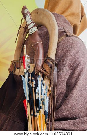 Historical set of old wooden arrows with bright plumage in the quiver on human back in the cloak a hood