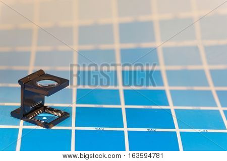 Magnifier or printer's loupe sits on a cyan test sheet in a pre-press workshop when proofing