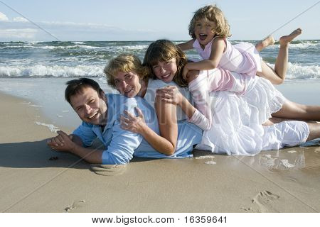 Happy family playing together on the beach