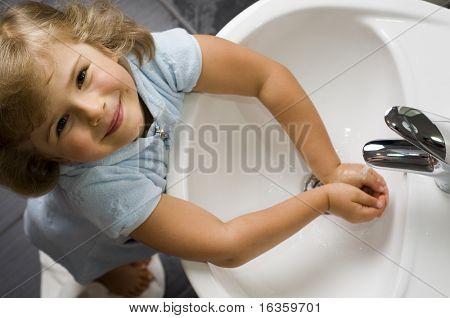 Cute girl washing hands in bathroom