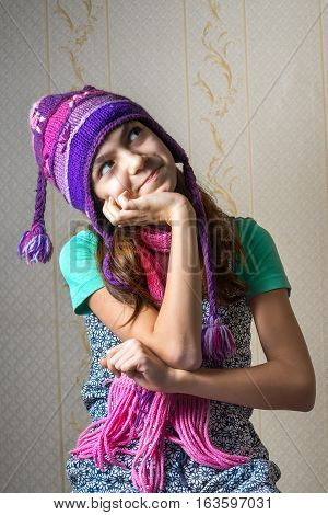 Portrait of a 11 year old girl in a shirt and a knitted hat and scarf looking up pensively.