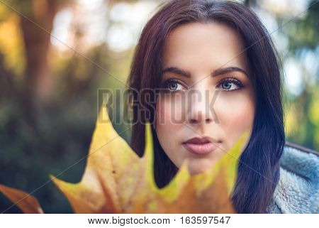 Thoughtful young woman in autumn woodland standing behind colorful yellow fall leaves in a concept of changing seasons and beauty