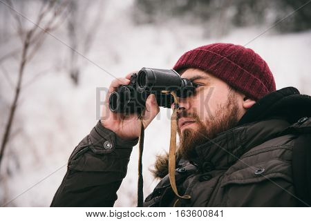 man sees nature through binoculars in the forest