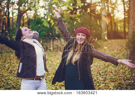 Two cute young woman celebrating autumn together in colorful woodland tossing handfuls of yellow leaves in the air with outstretched arms