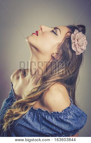 Sensual young woman in vintage fashion wearing an off the shoulder top and flower in her long hair standing with her head tilted back and eyes closed toned portrait