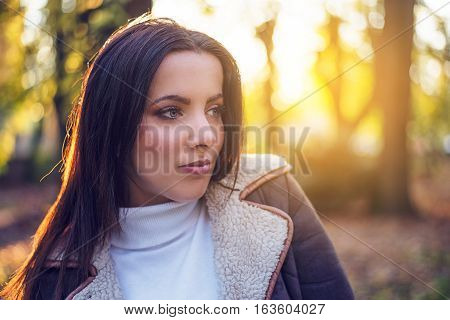 Thoughtful attractive young woman relaxing in evening sunshine backlit by its warm glow as she enjoys the changing fall season in colorful woodland