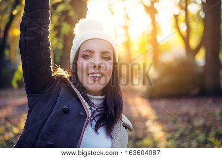 Happy pretty young woman in an autumn forest standing facing the camera waving with a smile against the bright warm glow of the evening sun