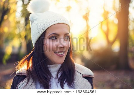 Attractive young woman wearing a white knitted hat with pompom enjoying an autumn evening outdoors in a wooded park looking to the side with a smile against the warm glow of the setting sun