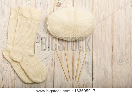 Knitted of white yarn socks yarn and knitting needles on a light wooden background.