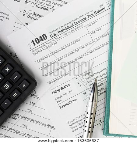 Close up U.S. Individual tax form 1040 with calculator and pen.