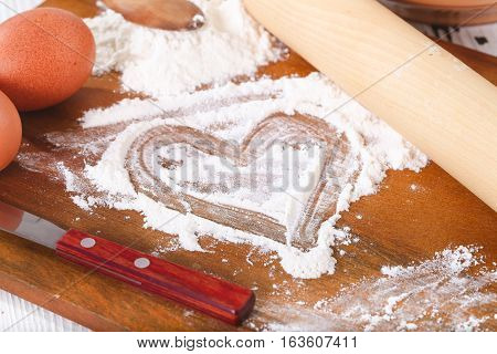 The heart drawn on flour. Kitchen board eggs and ware around. On a board flour on which heart is drawn is scattered