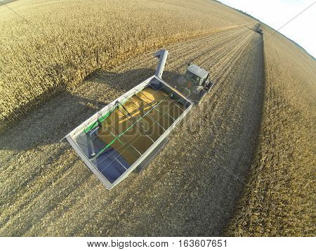 Aerial sot of a JD tractor and JD track driven grain cart hauling corn.