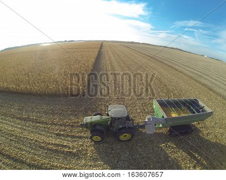 Aerial side view of a green tractor pulling a grain bin with track drive.  Set in a corn field.