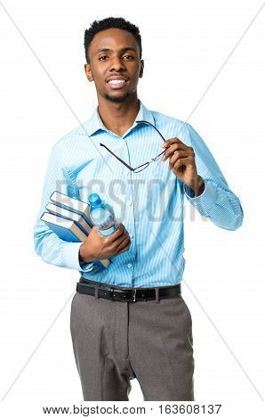 Happy african american college student standing with books and bottle of water in his hands on white background