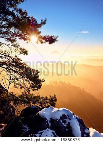 Freeze Daybreak, Rocks With Fresh Powder Snow. Peak Above Fog