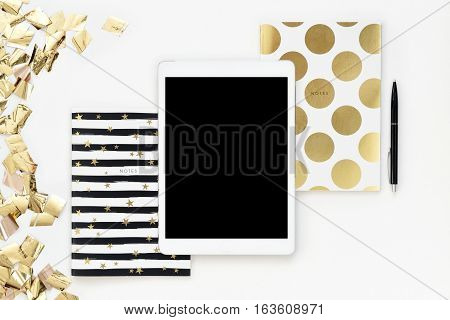 Flat lay photo of office white desk with tablet and gold notebook with copy space background. Mock up template. Party serpentine glitter
