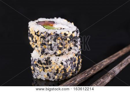Two rollas sesame and salmon on a black background