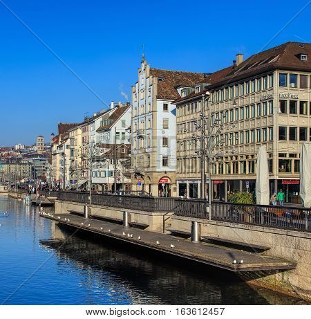 Zurich, Switzerland - 1 January, 2017: the Limmat river, historic buildings, people on the embankment, Christmas illumination lamps temporarily installed along it. Zurich is the largest city in Switzerland.