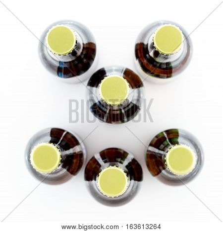 Pattern of six beer bottles with gold caps facing upwards and making a smiley face