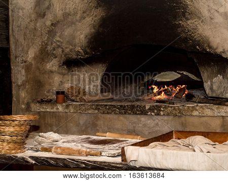 Baking flatbread on saj in outdoor oven in Nazareth Village Israel