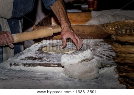 Man dressed in period clothes rolls the dough with rolling pin hands close-up in Nazareth Village Israel