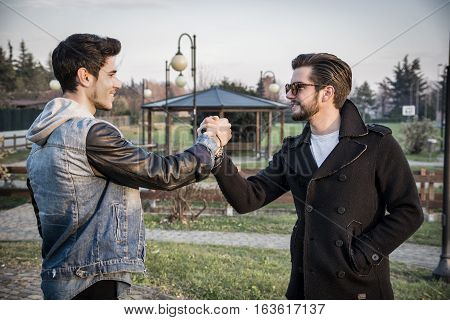 Two handsome casual trendy young men greeting outdoors in an urban park gripping hands with happy welcoming smiles