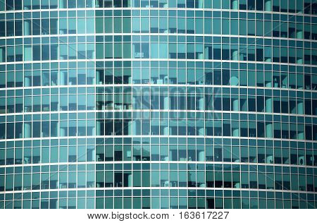 Glass wall of modern office building with many large panoramic windows in business cluster front view closeup
