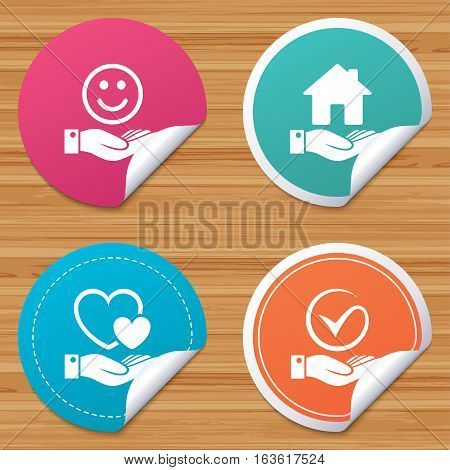 Round stickers or website banners. Smile and hand icon. Heart and Tick or Check symbol. Palm holds house building sign. Circle badges with bended corner. Vector