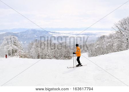 Skier taking in the beautiful Myoko scenery before continuing down the mountain. Distant mountain ranges are partially covered by low lying clouds.