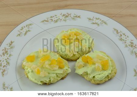 Three frosted key lime sugar cookies on plate