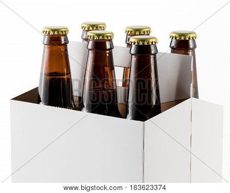 Six beer bottles in cardboard container with gold caps with corner of carrier facing camera