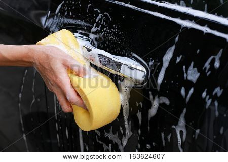 Washing car.Female hand with yellow sponge washing car