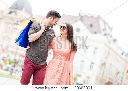 Cheerful couple shopping together in the city.