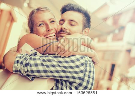 Beautiful young loving couple carrying shopping bags on shoulders and enjoying together.