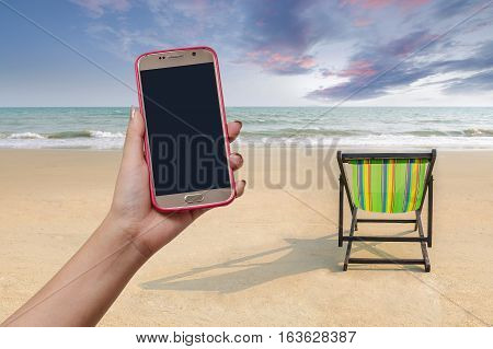 Beach chair and shadow with woman hand hold close mobile on white sand beach with sunset light sky (lonely concept)