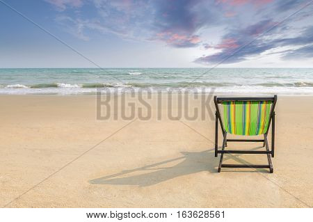 Beach chair and shadow on the white sand beach with sunset light sky (lonely concept)