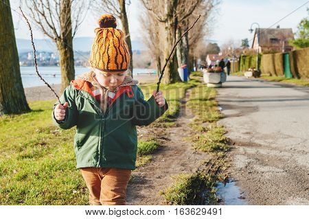 Cute 3 year old little boy playing outdoors on sunny early spring day, wearing green jacket and orange hat
