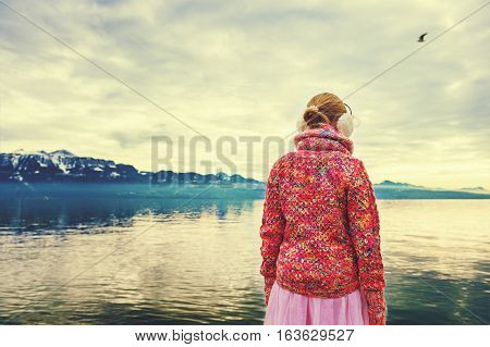Adorable little girl admiring lake Geneva on a cold winter day, wearing warm pink pullover and earmuffs, back view