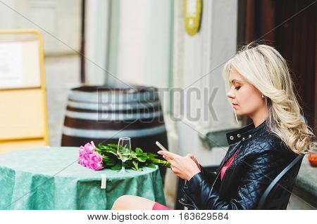 Outdoor portrait of beautiful blond woman holding bouquet of pink roses, resting in cafe, using smartphone