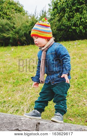 Adorable toddler boy playing in park, wearing colorful hat, denim jacket and green trousers