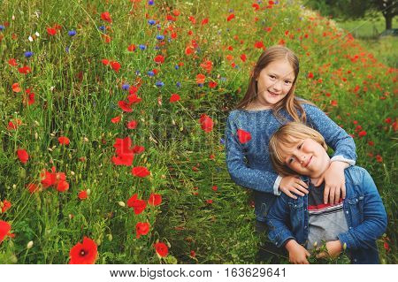 Outdoor portrait of two cute kids playing in poppy field