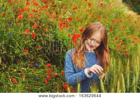 Outdoor portrait of adorable little blond girl of 8-9 years old in poppy field
