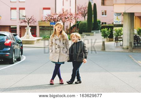Two fashion kids models posing outdoors on nice spring day, wearing stylish jackets