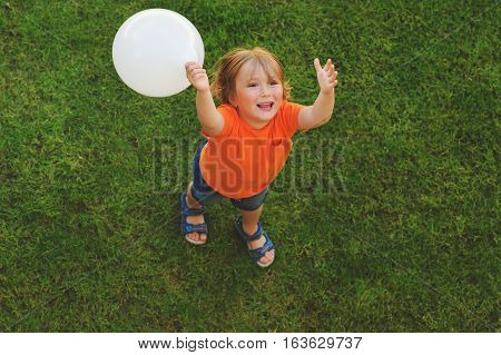 Happy little boy of 4-5 years old playing with white balloon outdoors, top view