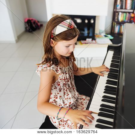 Little girl playing piano at home, musical education for kids