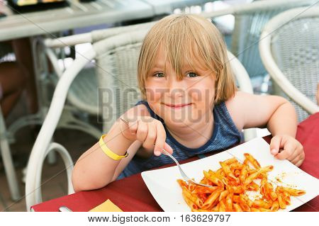 Adorable toddler boy eating pasta with tomatoe sause in restaurant